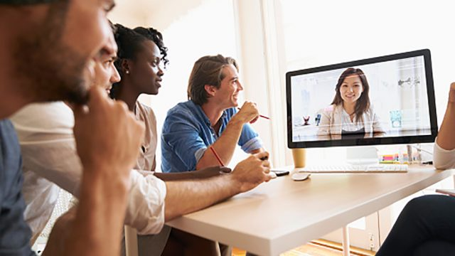 People talking on video conference in office